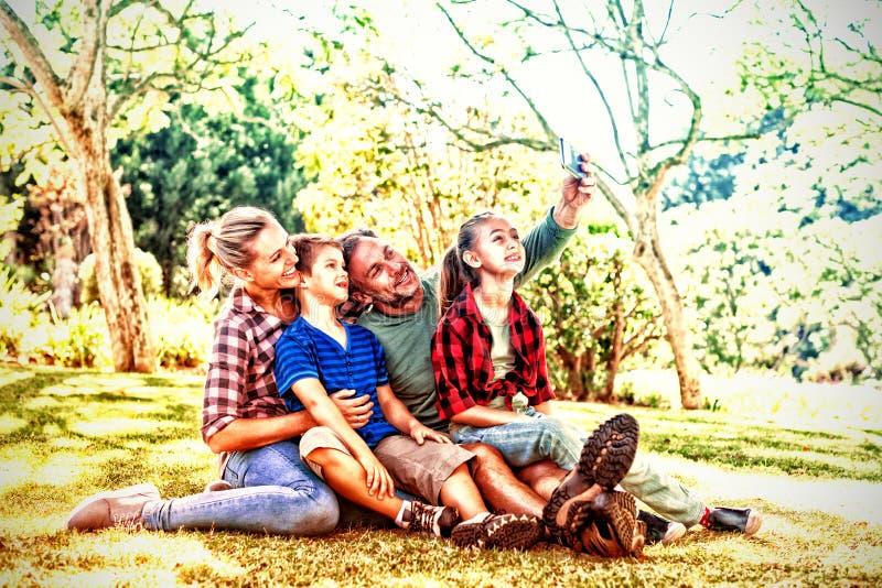 Szczęśliwa rodzina bierze selfie w parku zdjęcia stock