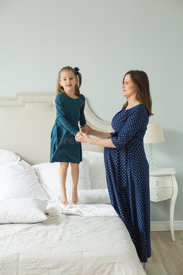 szczęśliwa rodzina Ciężarna matka i mały córki doskakiwanie obrazy stock