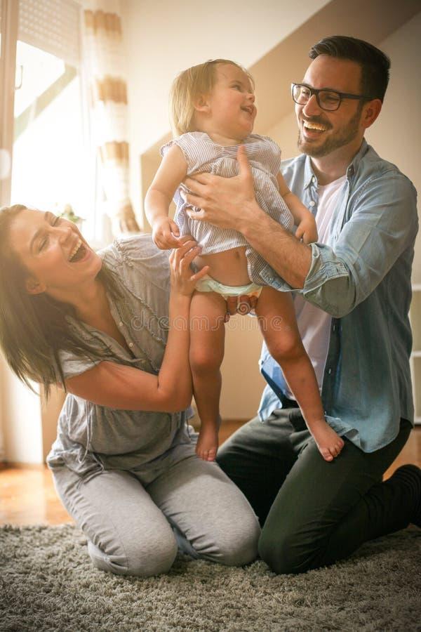 Szczęśliwa rodzina cieszy się w domu z ich małym dzieckiem obraz royalty free