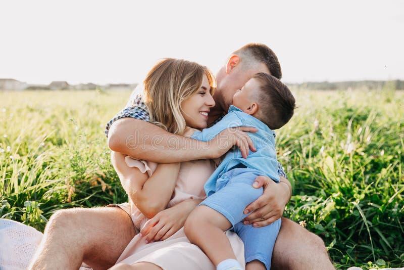 Szczęśliwa rodzina cieszy się wpólnie w letnim dniu Rodzinny obsiadanie na trawie i obejmowaniu obrazy stock