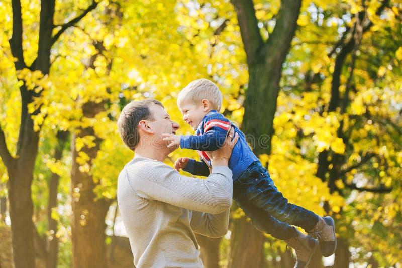 Szczęśliwa rodzina dwa ludzie śmia się i bawić się w jesieni drewnie zdjęcie royalty free