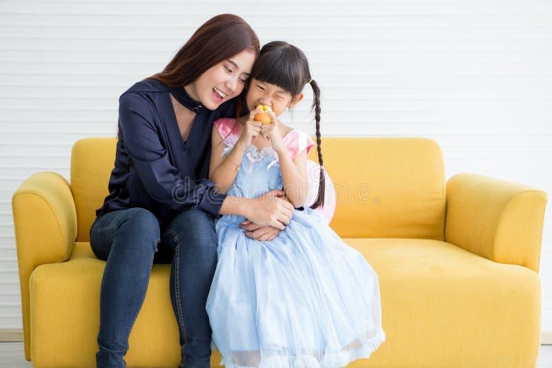 Szczęśliwa rodzina i dzieciaki ma śniadaniowego obsiadanie na kanapie, Macierzysty łasowania jabłko wraz z córka ranku styl życia obraz royalty free