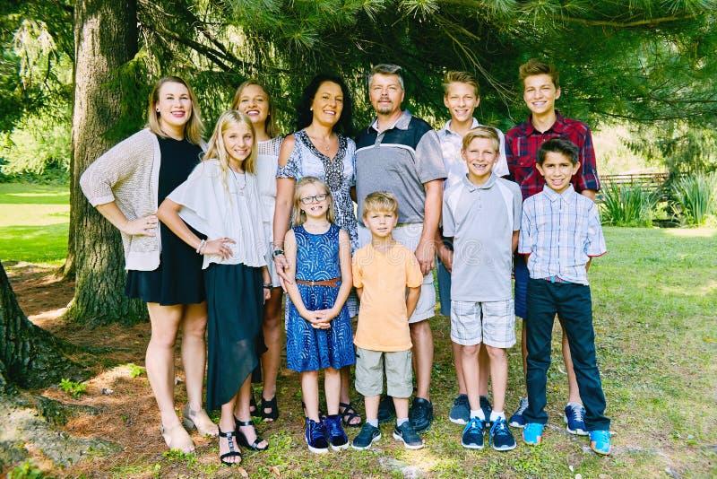 Szczęśliwa rodzina jedenaście ludzi stoi pod trzy zdjęcia royalty free