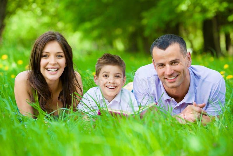 Szczęśliwa rodzina kłama na trawie z książką trzy zdjęcia stock