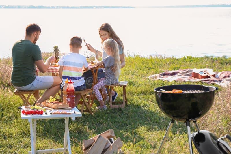 Szczęśliwa rodzina ma lunch przy stołem na lato pinkinie zdjęcie stock