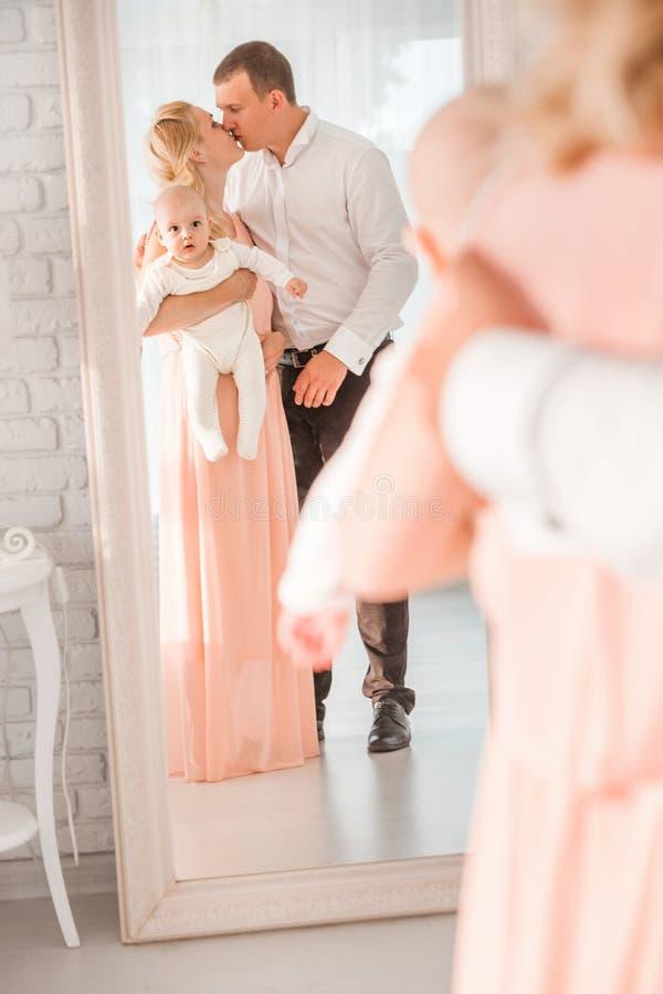 Szczęśliwa rodzina mama, tata i syn blisko lustra -, zdjęcie royalty free