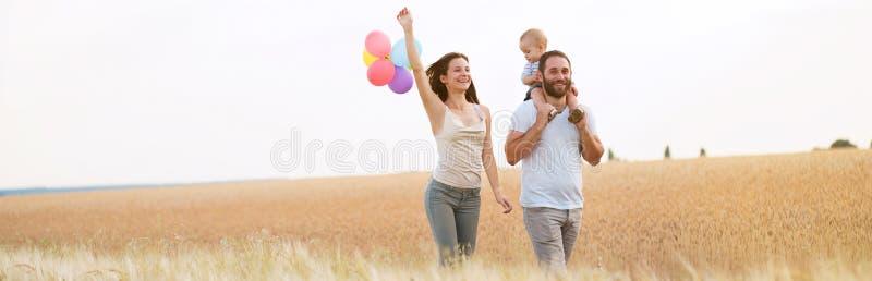 Szczęśliwa rodzina mama, tata i syn chodzi outdoors, zdjęcie royalty free