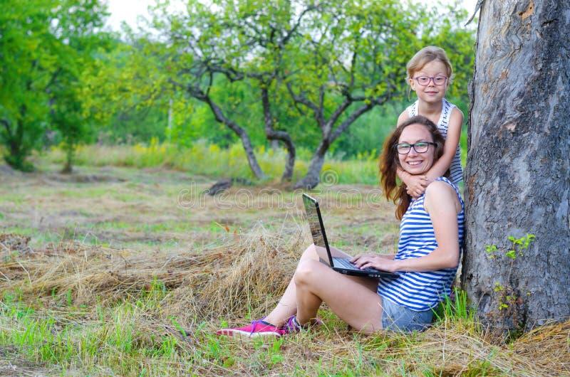 Szczęśliwa rodzina: matka i córka pracuje na laptopie w naturze, fotografia stock
