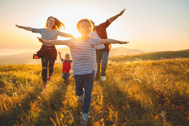 Szczęśliwa rodzina: matka, ojciec, dzieci synowie i córka na sunse, zdjęcie stock