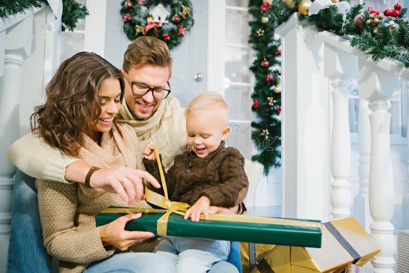Szczęśliwa rodzina - matka, ojciec i syn, odpakowywamy Bożenarodzeniowych prezenty obraz stock