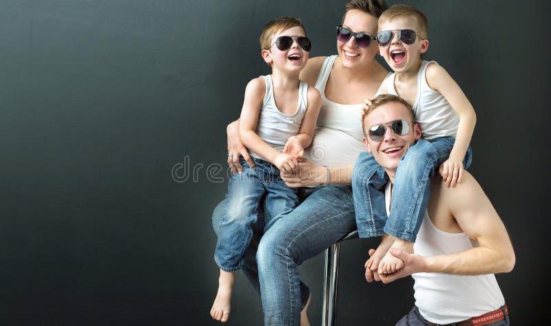 Szczęśliwa rodzina na czarnym pracownianym tle zdjęcie royalty free