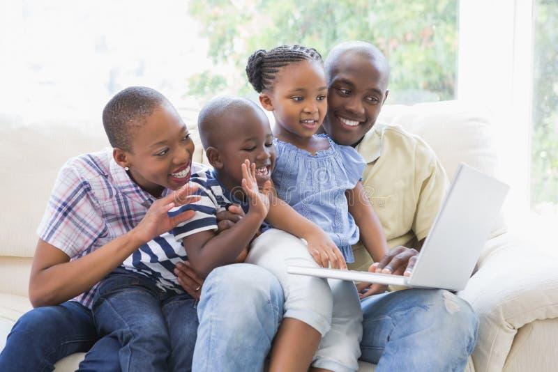 Szczęśliwa rodzina na leżanki gawędzeniu z laptopem zdjęcia stock