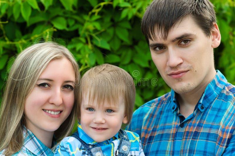 Szczęśliwa rodzina na tło zieleni żywopłocie obrazy stock