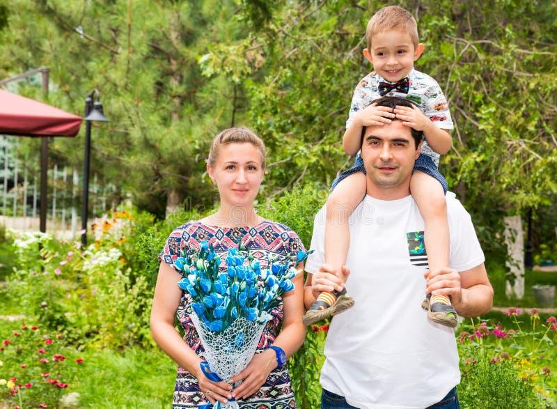 Szczęśliwa rodzina ojciec, matka i dziecko w plenerowym na letnim dniu, Portreta dzieciak na naturze i rodzice Pozytywne ludzkie  fotografia royalty free