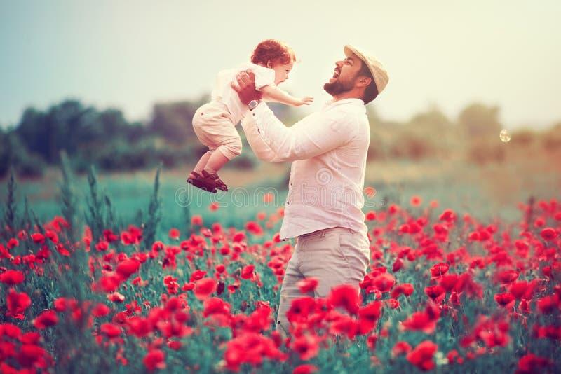 Szczęśliwa rodzina, ojciec z dziecięcą chłopiec bawić się w makowym kwiatu polu przy letnim dniem zdjęcia stock