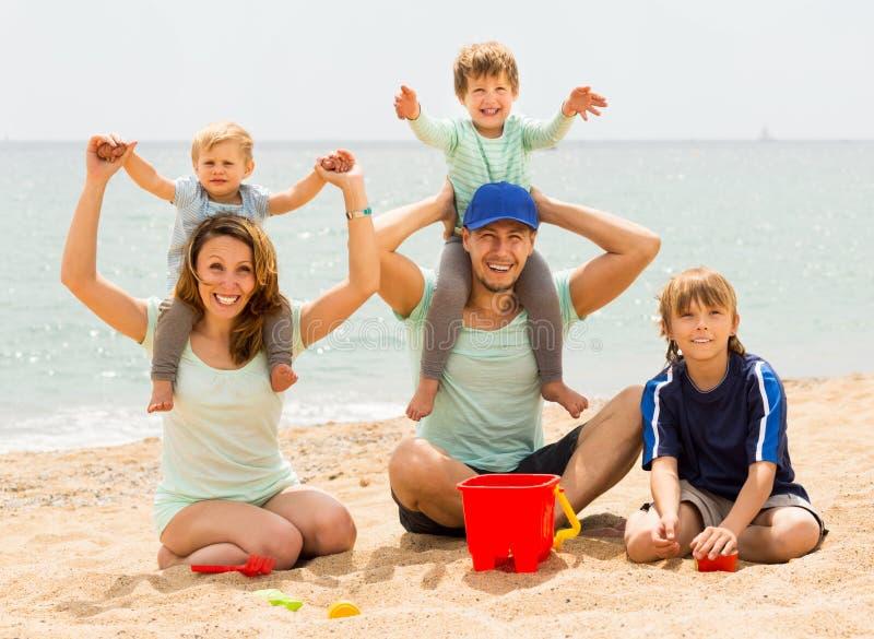 Szczęśliwa rodzina ono uśmiecha się przy morze plażą pięć obrazy royalty free