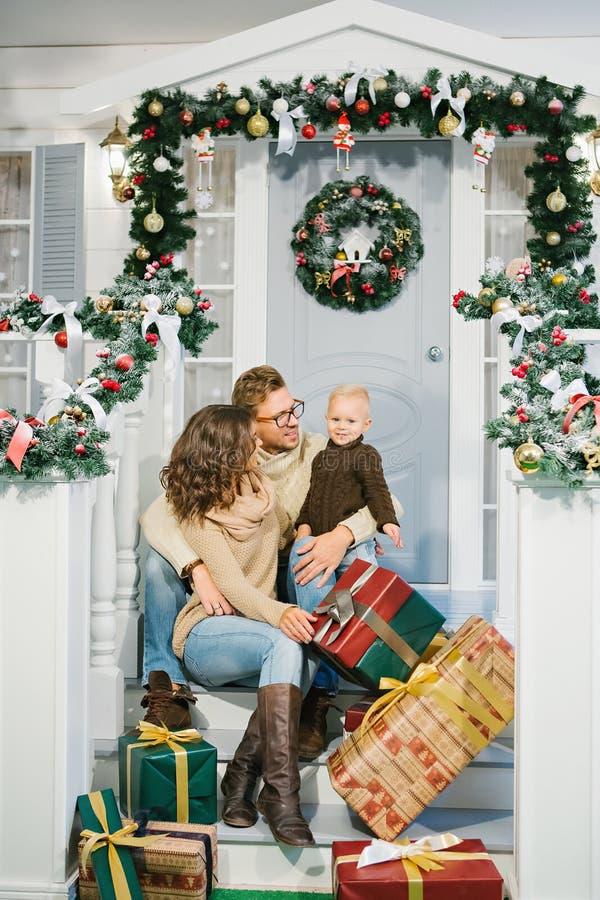 Szczęśliwa rodzina, otaczająca z Bożenarodzeniowymi prezentami zdjęcia stock