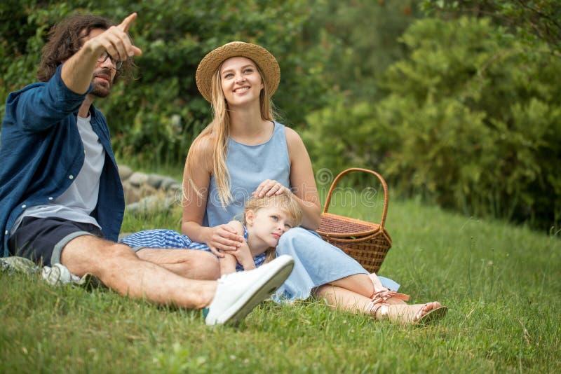 Szczęśliwa rodzina picnicking outdoors z ich śliczną córką, błękitów ubrania, kobieta w kapeluszu obraz stock