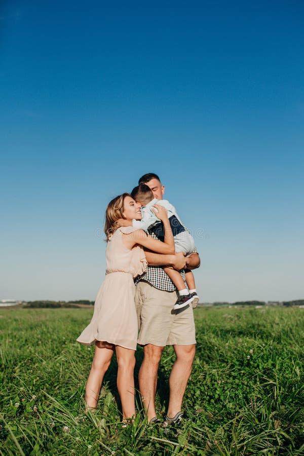 Szczęśliwa rodzina: potomstwa ojcują przy letnim dniem, matka, jego mały syna przytulenie w polu i odprowadzenie i zdjęcia stock