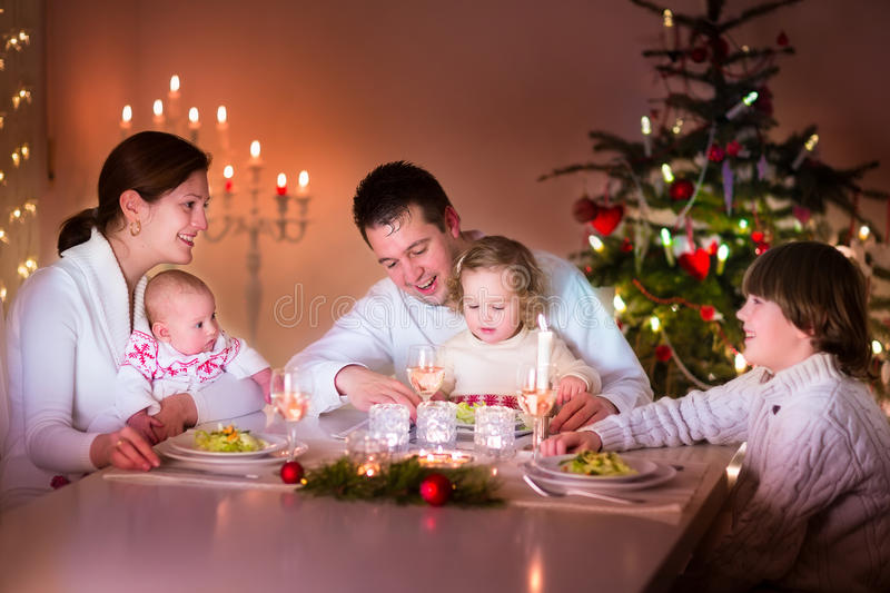 Szczęśliwa rodzina przy Bożenarodzeniowym gościem restauracji obrazy stock