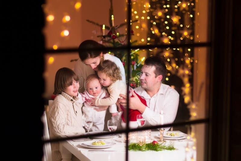 Szczęśliwa rodzina przy Bożenarodzeniowym gościem restauracji obraz stock