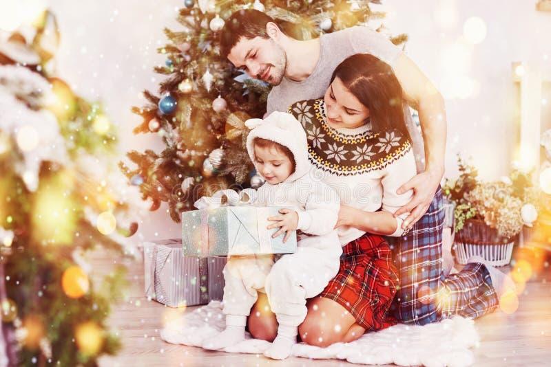 Szczęśliwa rodzina przy bożymi narodzeniami w ranku otwarcia prezentach blisko jedlinowego drzewa wpólnie Pojęcie rodzinny szczęś zdjęcia stock
