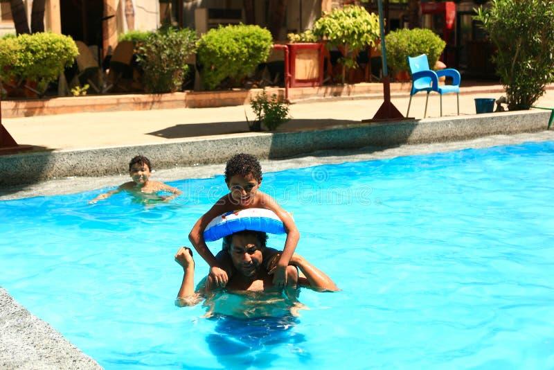 Szczęśliwa rodzina przy pływackim basenem zdjęcia royalty free