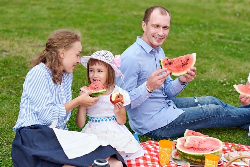 Szczęśliwa rodzina przy pyknicznym łasowanie arbuzem Matka, ojciec i dziecko przy pinkinem w, łące lub parku zdjęcie stock