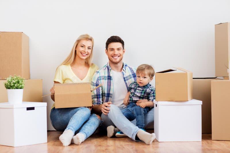 Szczęśliwa rodzina rusza się nowy dom z pudełkami zdjęcie stock