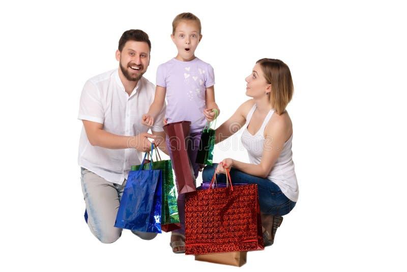Szczęśliwa rodzina siedzi przy studiiem z torba na zakupy zdjęcie royalty free