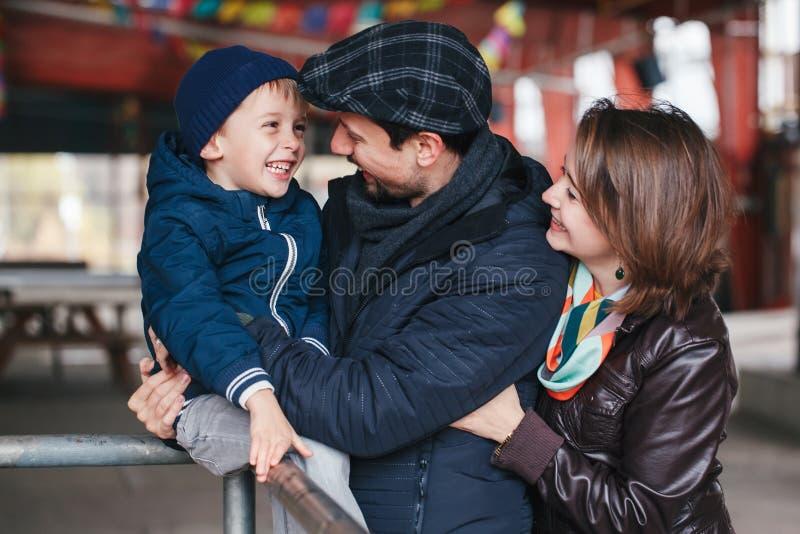 szczęśliwa rodzina trzy matka, ojciec i syn ono uśmiecha się, śmiający się opowiadać each inny, zdjęcia stock