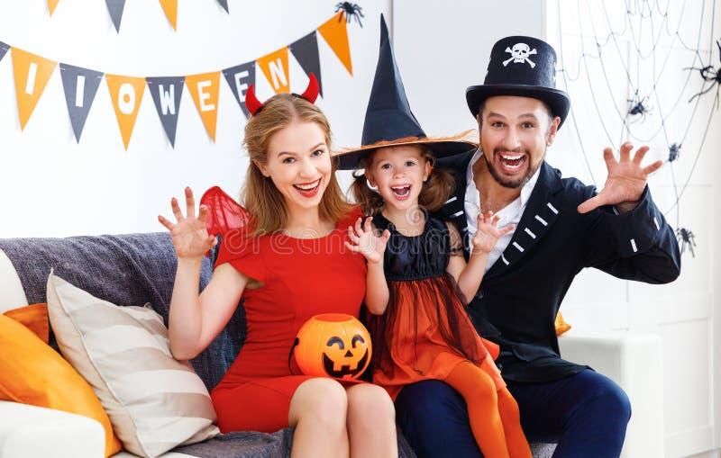 Szczęśliwa rodzina w kostiumach dostaje przygotowywający dla Halloween w domu obrazy stock