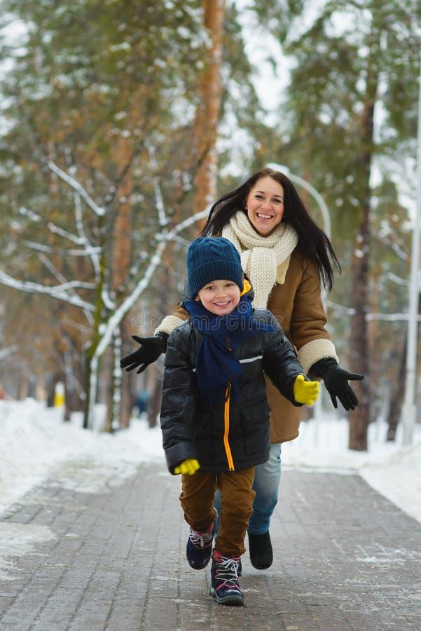 Szczęśliwa rodzina w zimy odzieży Uśmiechnięty syn biega zdala od jego matki plenerowej obraz royalty free