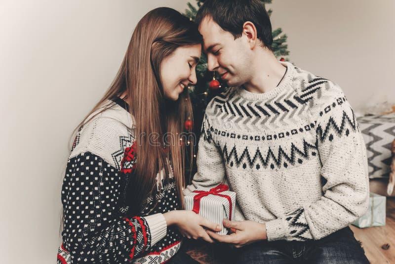 Szczęśliwa rodzina wymienia prezenty w świątecznym roo w eleganckich pulowerach obraz royalty free