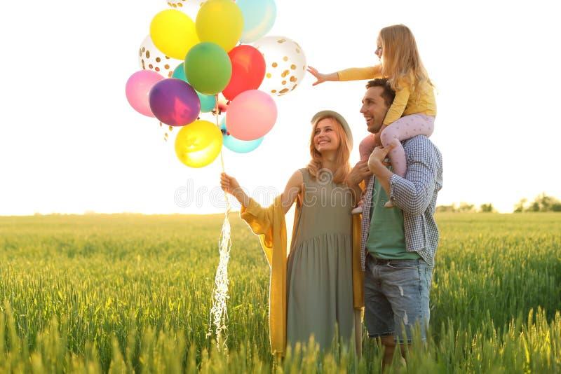 Szczęśliwa rodzina z balonami outdoors na słonecznym dniu fotografia royalty free