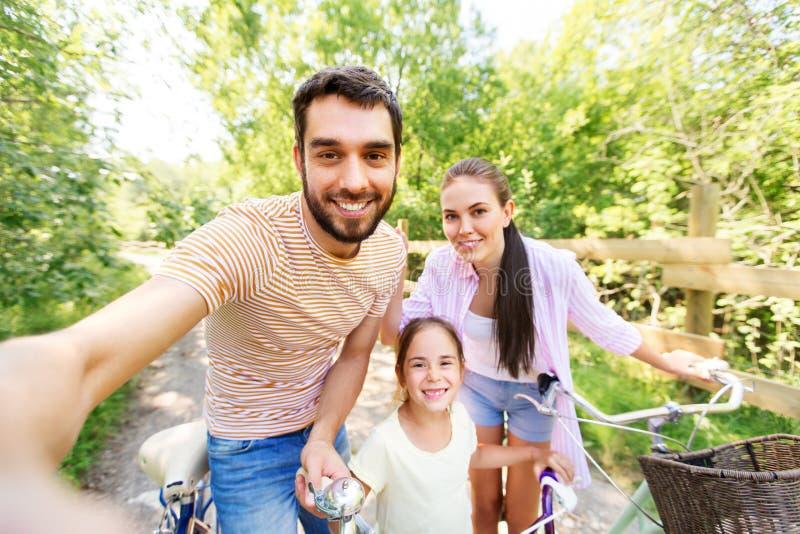 Szczęśliwa rodzina z bicyklami bierze selfie w lecie obrazy royalty free