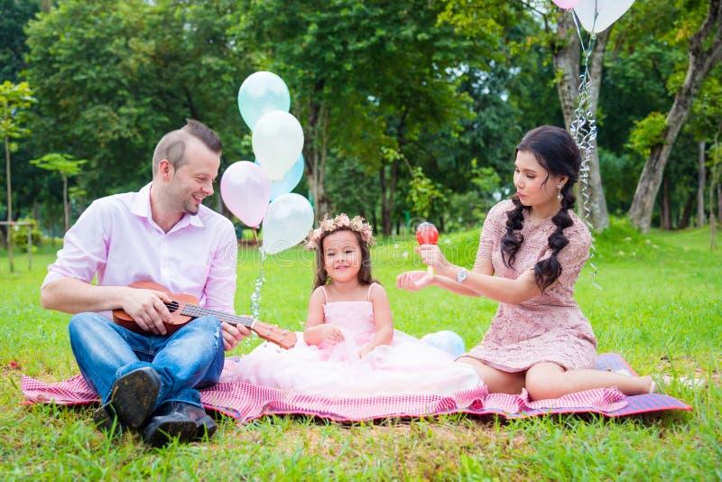 Szczęśliwa rodzina z córką bawić się muzykę i śpiewa piosenkę obraz royalty free