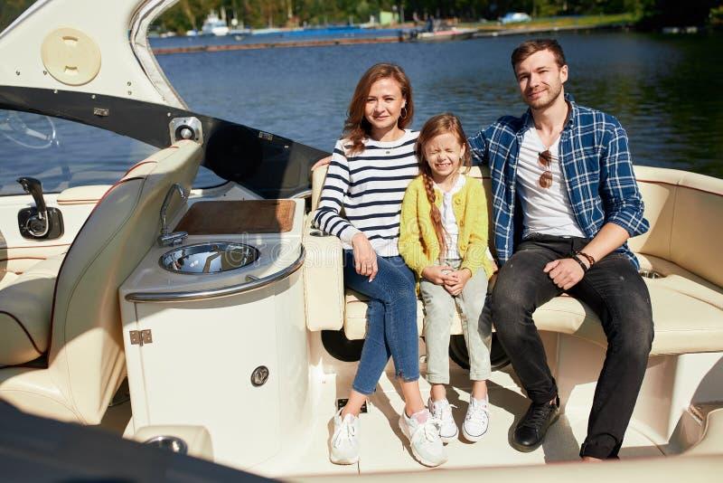 Szczęśliwa rodzina z córką na żeglowanie łodzi przy pogodnym jesień dniem zdjęcie royalty free