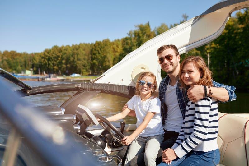 Szczęśliwa rodzina z córką na żeglowanie łodzi przy pogodnym jesień dniem obrazy royalty free