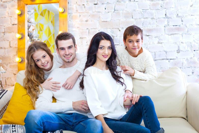 Szczęśliwa rodzina z dwa dziećmi chłopiec i dziewczyny obsiadanie na leżance w lekkich bluzkach i niebieskich dżinsach Boże Narod zdjęcia stock