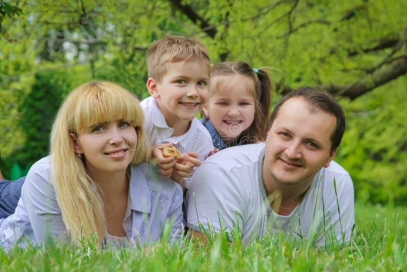 Szczęśliwa rodzina z dwa dziećmi kłama na trawie obrazy royalty free