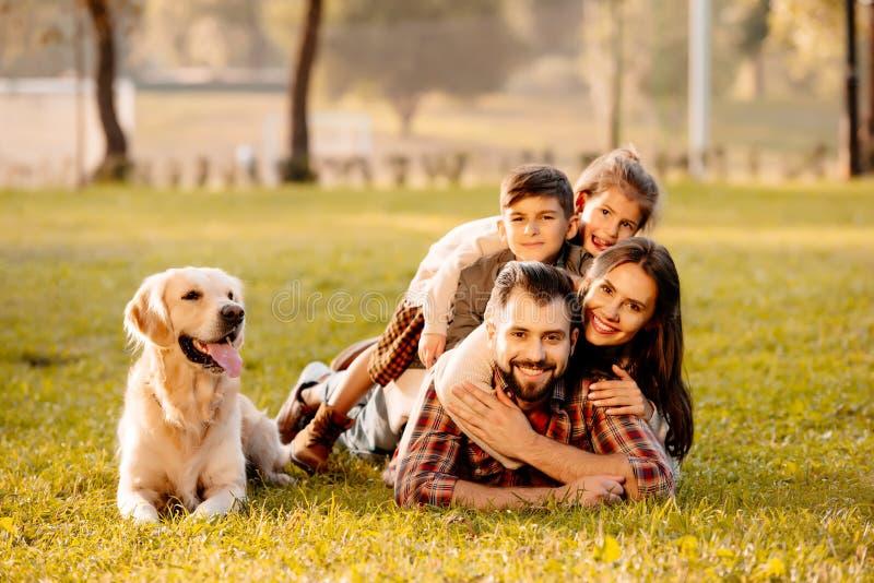 Szczęśliwa rodzina z dwa dziećmi kłama w stosie na trawie z psim obsiadaniem obraz royalty free