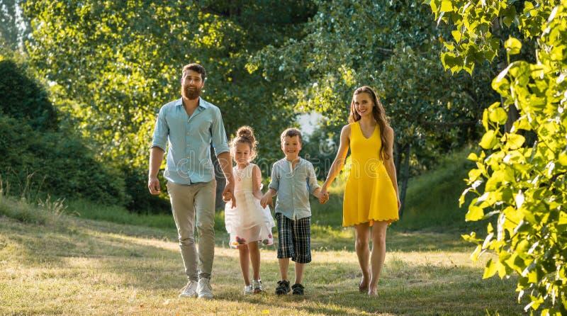 Szczęśliwa rodzina z dwa dziećmi trzyma ręki podczas rekreacyjnego spaceru zdjęcia royalty free