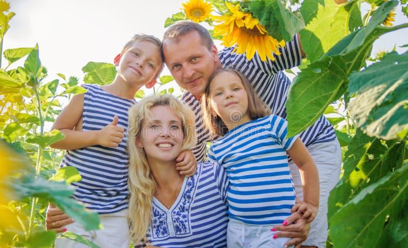 Szczęśliwa rodzina z dwa dziećmi w słonecznikach zdjęcia stock