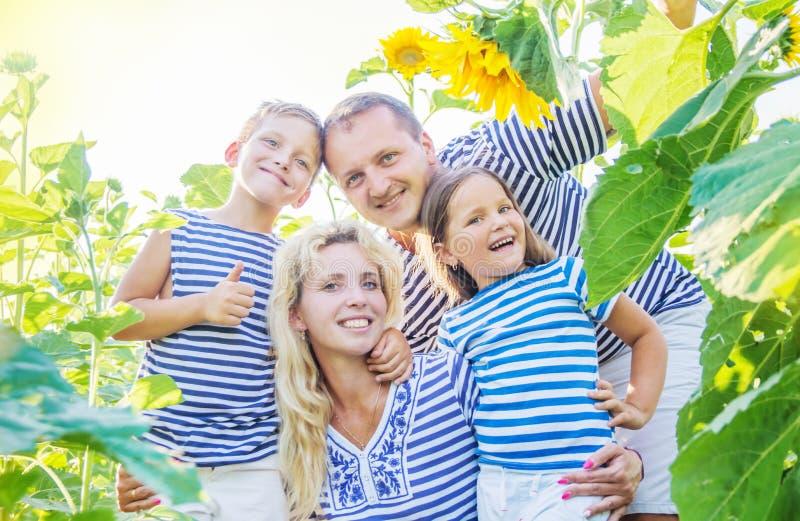 Szczęśliwa rodzina z dwa dziećmi w słonecznikach zdjęcia royalty free