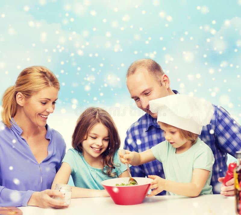 Szczęśliwa rodzina z dwa dzieciakami robi sałatki w domu zdjęcie stock