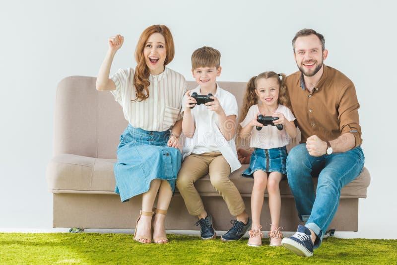 szczęśliwa rodzina z dwa dzieciakami siedzi na leżance i bawić się obrazy stock