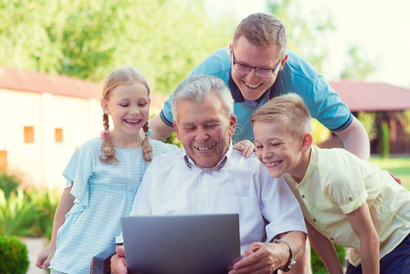 Szczęśliwa rodzina z dziadem opowiada na laptopie podczas interneta fotografia royalty free