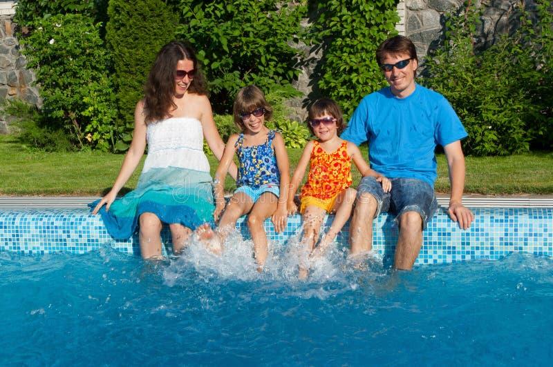 Szczęśliwa rodzina z dzieciakami ma zabawa pobliskiego basenu na wakacje zdjęcie stock