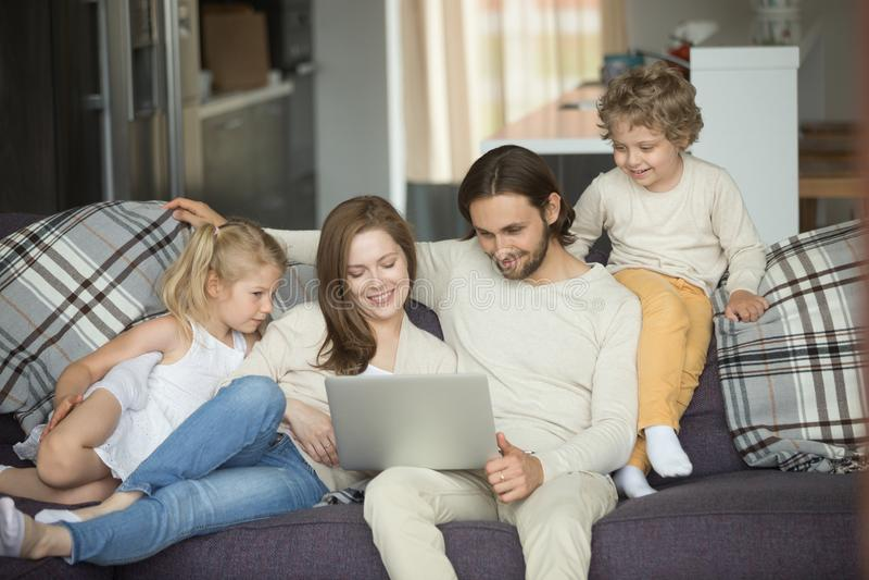 Szczęśliwa rodzina z dzieciakami używa laptop na kanapie w domu zdjęcie royalty free